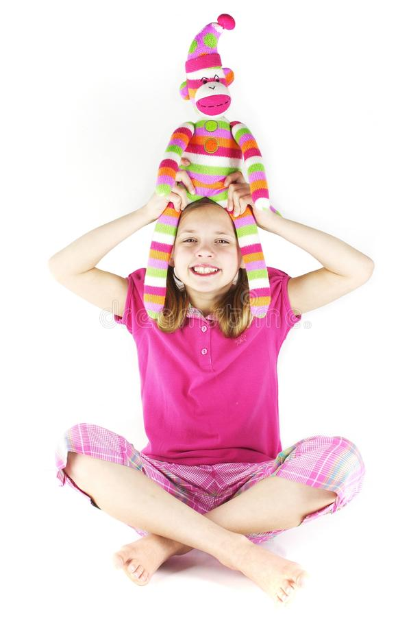 Fun with Sock Monkey. Smiling blond girl with sock monkey on her head. Happy and cheerful royalty free stock photography
