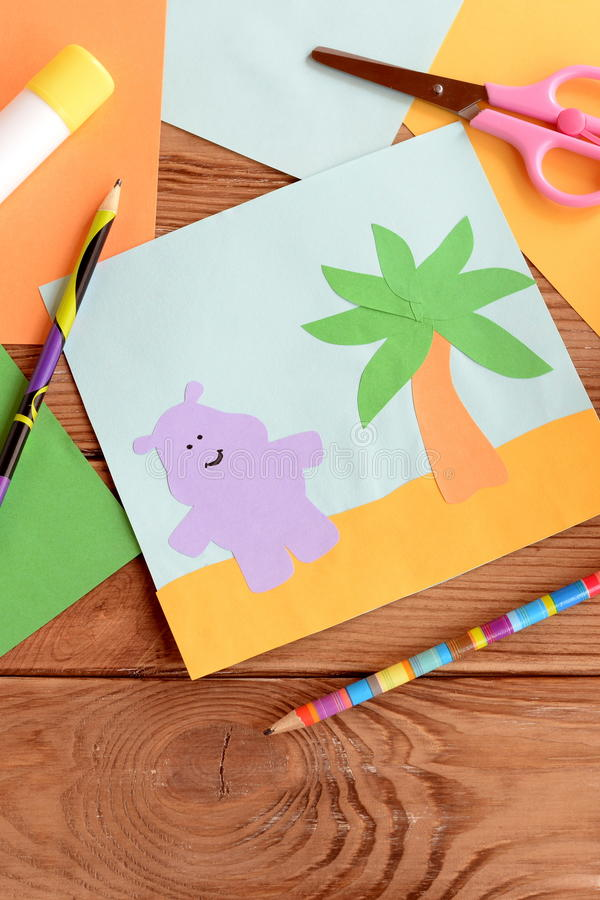 Fun summer card with a hippopotamus and a palm tree on a wooden table. Preschool and kindergarten crafts. Materials for kids art. Paper and glue crafts activity royalty free stock photo