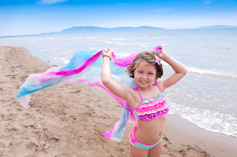 Fun Summer Vacations. Little Girls playing with a rainbow cloth at the beach, Summer Vacations royalty free stock photo