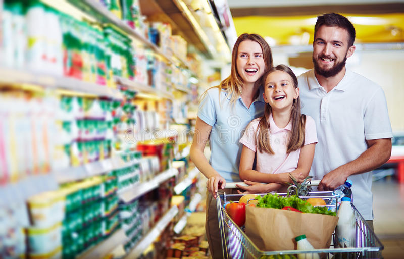 Fun in supermarket. Ecstatic family with shopping cart with food visiting supermarket