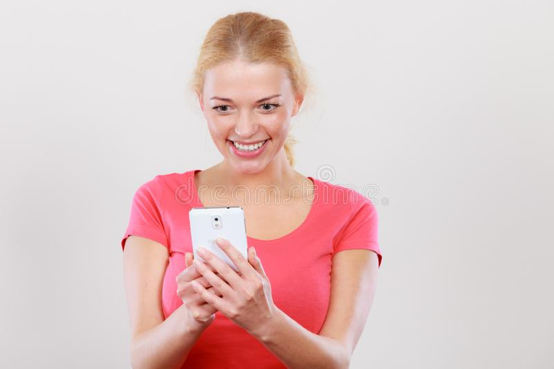 Excited, happy blonde woman using smartphone. Fun with technology, modern devices concept. Attractive, smiling, happy excited blonde woman checking social media stock image