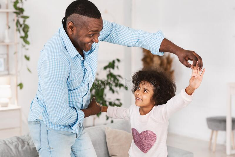 Fun times with grandpa. Older African American man dancing with pretty granddaughter at home. Fun times with grandpa. Older African American men dancing with his stock photos