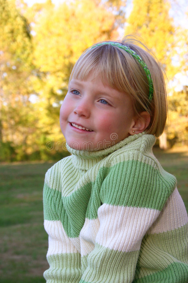Fun to be cute. Little girl smiles in the Autumn Sunset stock image