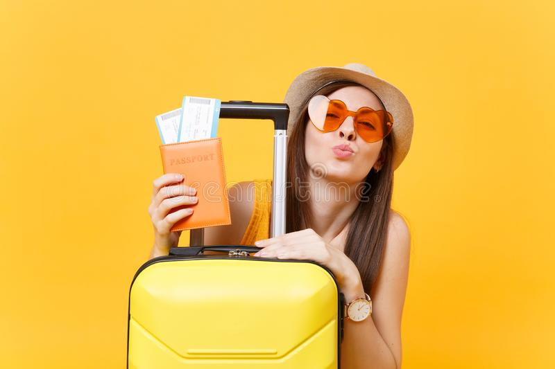 Fun tourist woman in summer casual clothes, hat, orange sunglasses with suitcase, passport on yellow background stock images