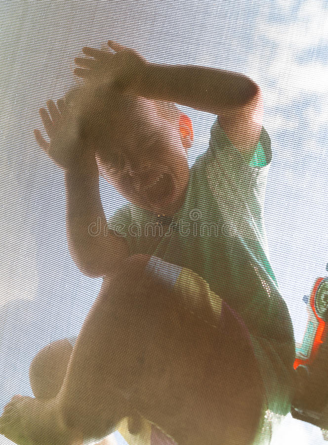 Fun on trampoline. Boy having fun jumping on trampoline (view from under the net royalty free stock photography
