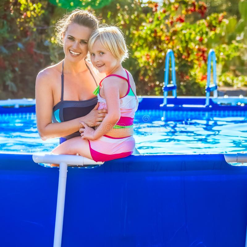 Smiling healthy mother and child in swimwear in swimming pool stock images