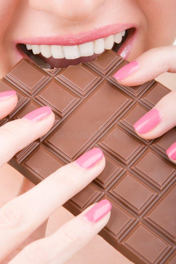 Fun woman eating chocolate stock photos