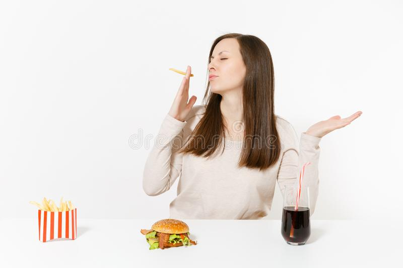Fun woman at table smoking piece of potatoes like cigarette, french fries, burger, cola in glass bottle isolated on. White background. Proper nutrition or royalty free stock photography
