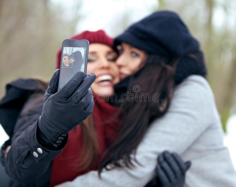 Fun Women Outdoors Taking Pictures with a Smart Phone stock photo