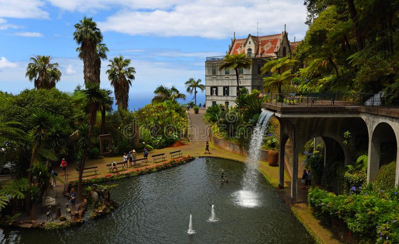 Monte Palace Tropical Gardens waterfall and pond and mansion house. FUNCHAL, MADEIRA, PORTUGAL - JUNE 26, 2019: Monte Palace Tropical Gardens waterfall and pond royalty free stock photos