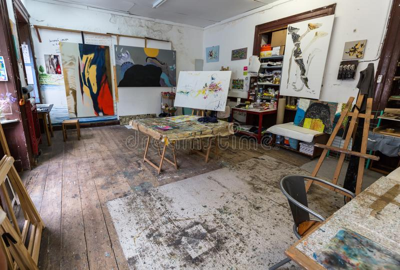 Open plan artists studio with easel, watercolours and hanging paintings in Funchal on Madeira. Portugal royalty free stock photography