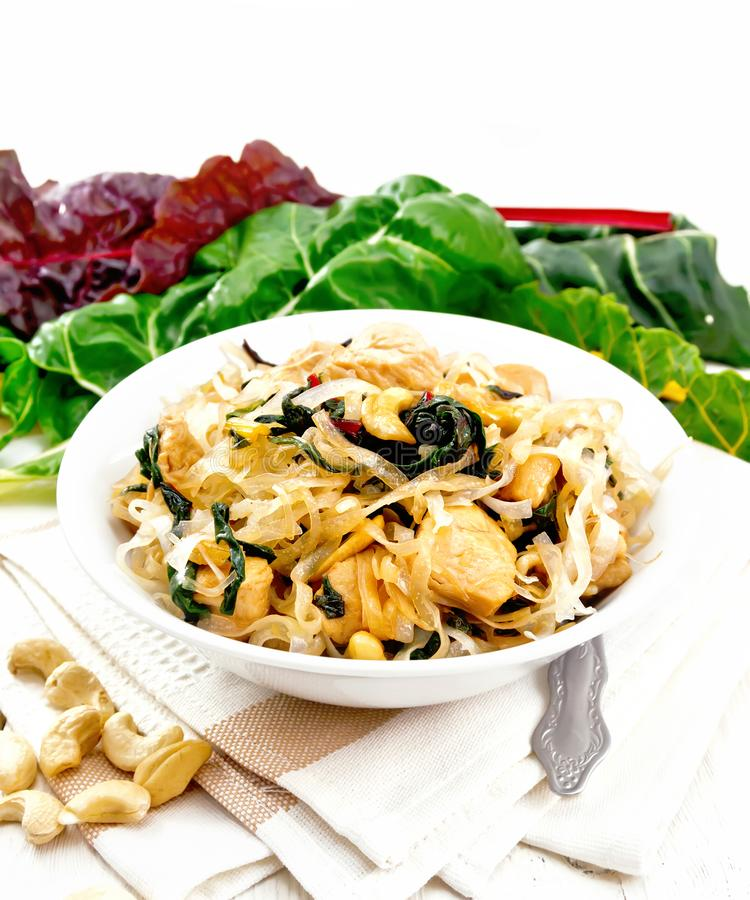 Funchoza with chard and cashew in bowl on board. Rice noodles with leafy beet, chicken breast, cashew nuts and soy sauce in a bowl on kitchen towel on wooden stock photos