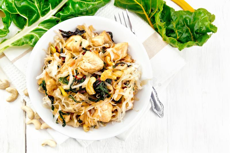 Funchoza with chard and cashew in bowl on board top. Rice noodles with leafy beet, chicken breast, cashew nuts and soy sauce in a bowl on a towel on wooden plank royalty free stock image