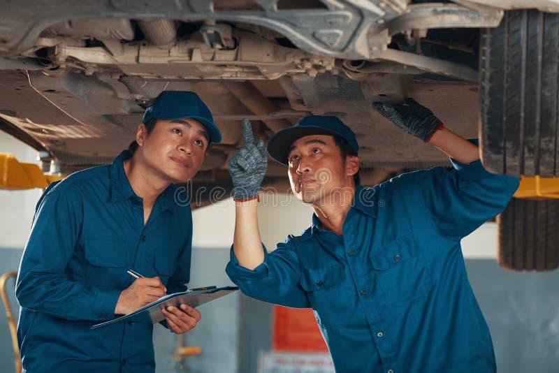Funcionários de serviço checando a parte inferior do carro imagem de stock