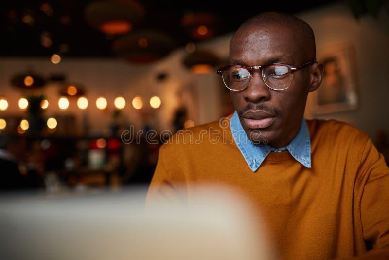 Funcionamento africano do homem com o portátil no café imagens de stock royalty free