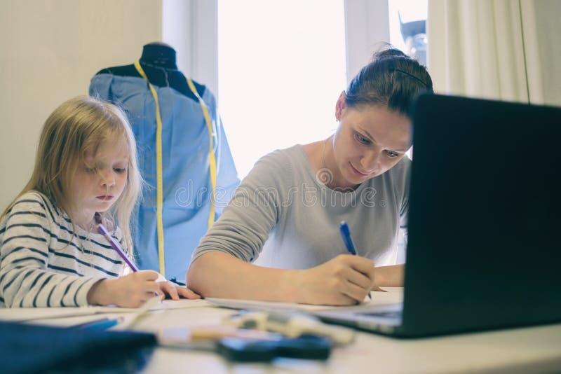 Funcionamento caucasiano da mulher quando sua imagem do desenho da filha perto dela foto de stock
