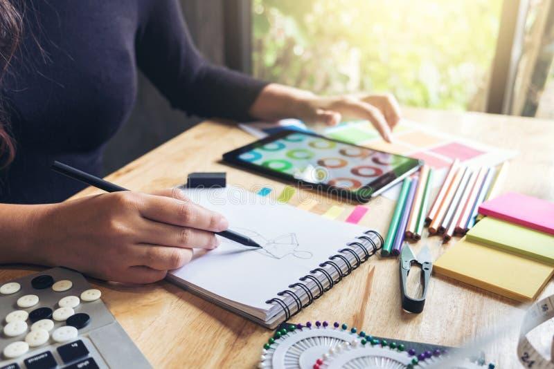 Funcionamento da costureira ou do desenhista da jovem mulher como desenhadores de moda fotos de stock royalty free