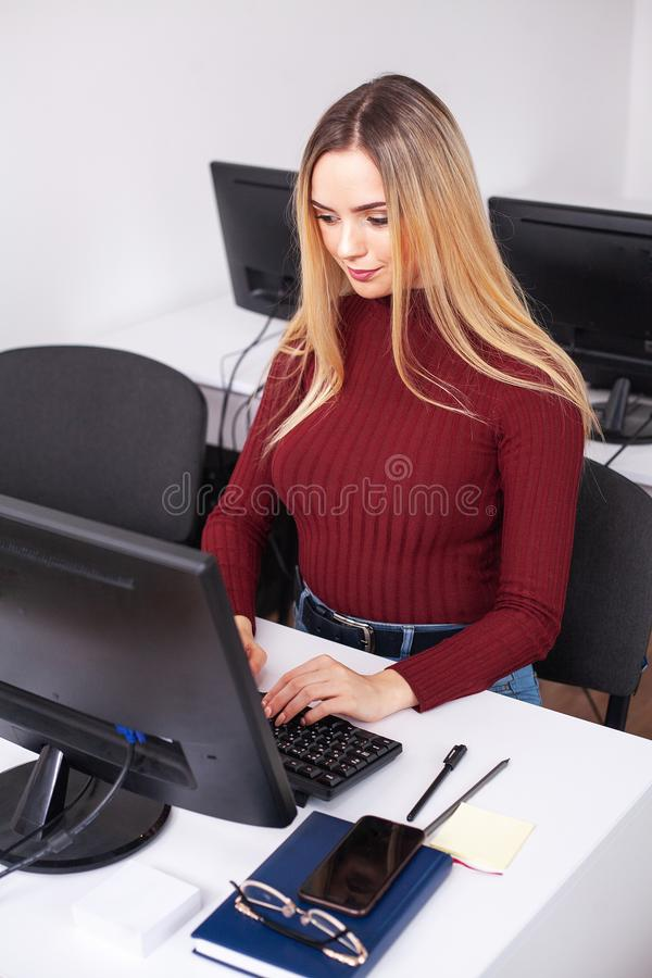 Funcionamento da jovem mulher e programação no computador no escritório imagem de stock royalty free