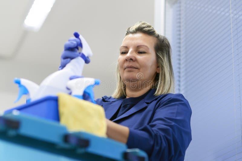 Funcionamento da mulher como o líquido de limpeza profissional no escritório imagem de stock royalty free