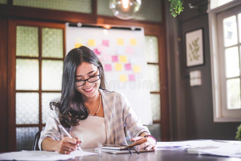 Funcionamento da mulher do negócio e nota asiáticos bonitos da escrita imagens de stock
