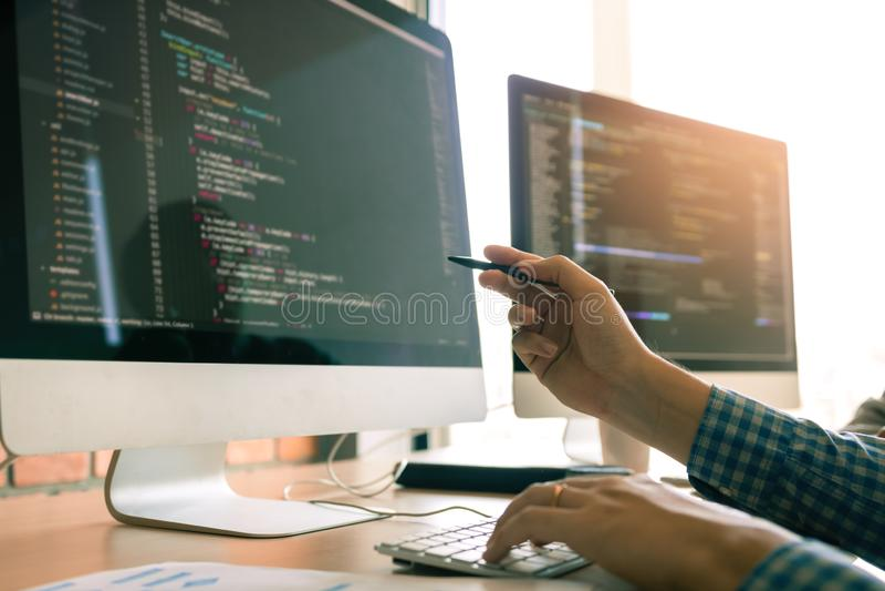 Funcionamento de programação tornando-se em aplicações de uma tecnologia do código das Software Engineers na mesa na sala do escr fotografia de stock