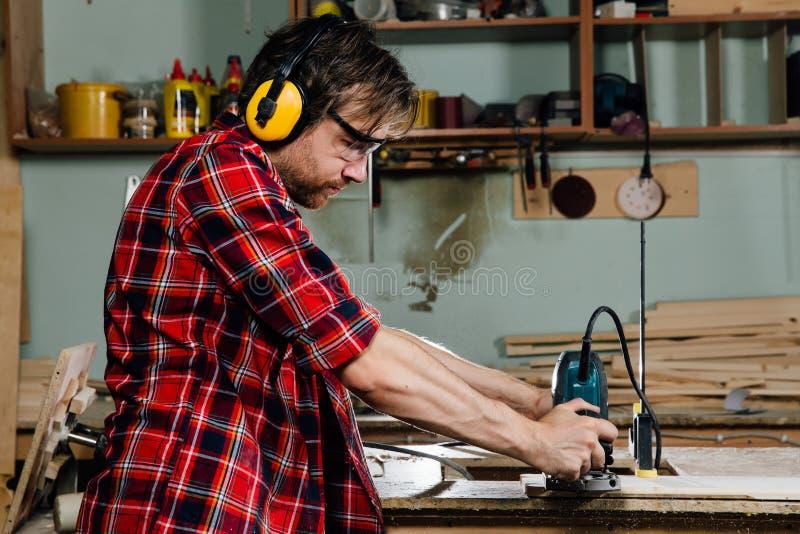 Funcionamento do carpinteiro da máquina de trituração manual da mão na oficina da carpintaria joiner imagens de stock royalty free