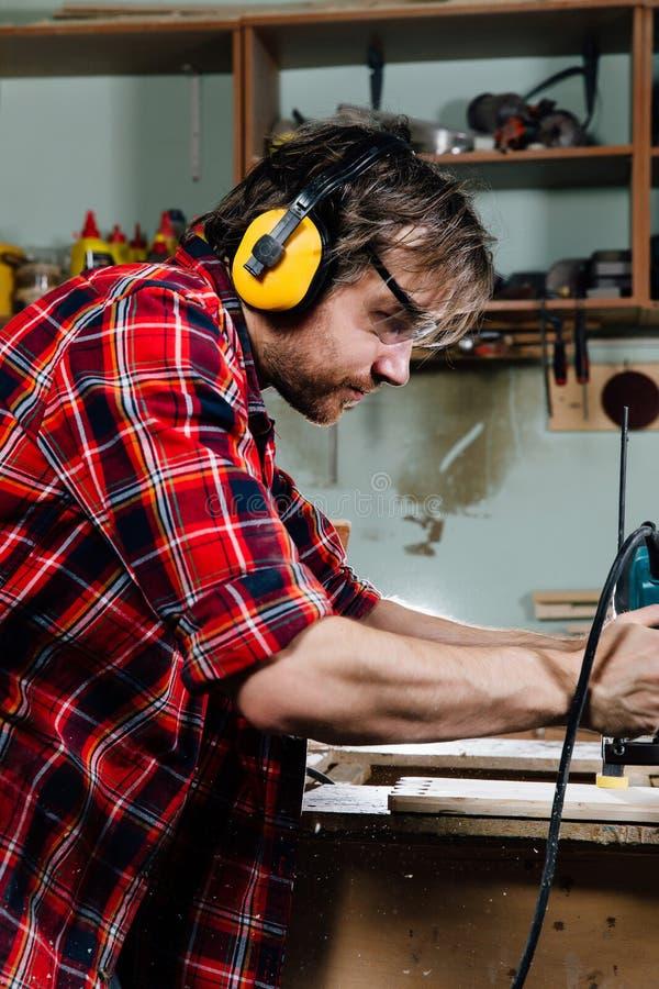 Funcionamento do carpinteiro da máquina de trituração manual da mão na oficina da carpintaria joiner foto de stock royalty free