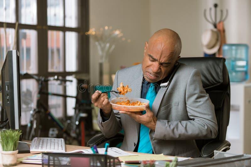 Funcionamento do homem através do almoço usando o telefone imagens de stock royalty free