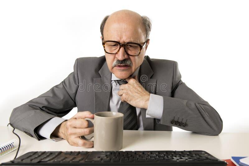 Funcionamento do homem de negócio 60s forçado e frustrado na mesa do portátil do computador de escritório que parece cansado e op imagens de stock