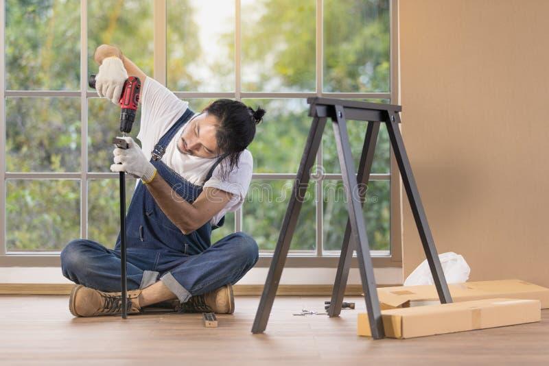 Funcionamento do homem novo como o trabalhador manual, tabela de madeira de montagem com equipm foto de stock royalty free