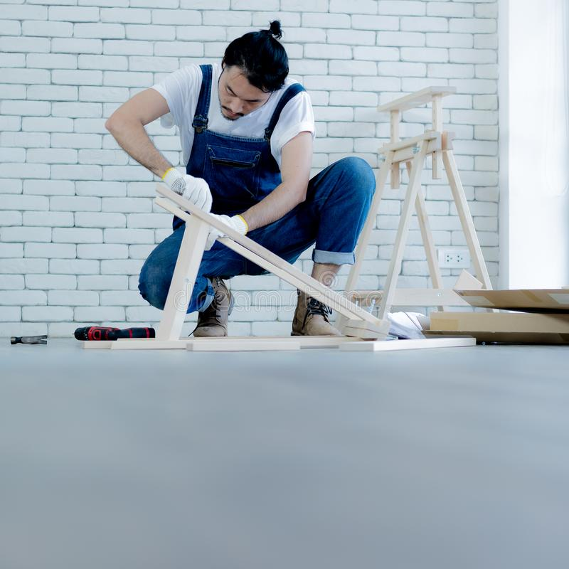 Funcionamento do homem novo como o trabalhador manual, tabela de madeira de montagem com equipm imagem de stock royalty free