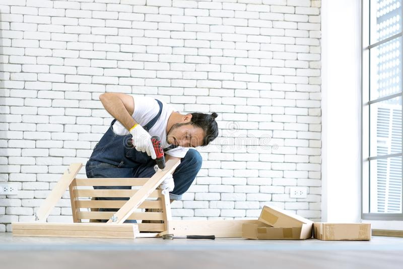 Funcionamento do homem novo como o trabalhador manual, tabela de madeira de montagem com equipm imagens de stock