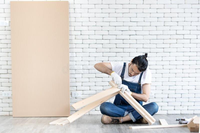 Funcionamento do homem novo como o trabalhador manual, tabela de madeira de montagem com equipm fotografia de stock royalty free