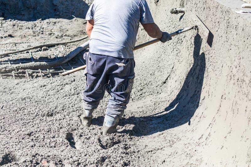 Funcionamento do trabalhador da constru??o da associa??o com um Bullfloat no concreto molhado foto de stock