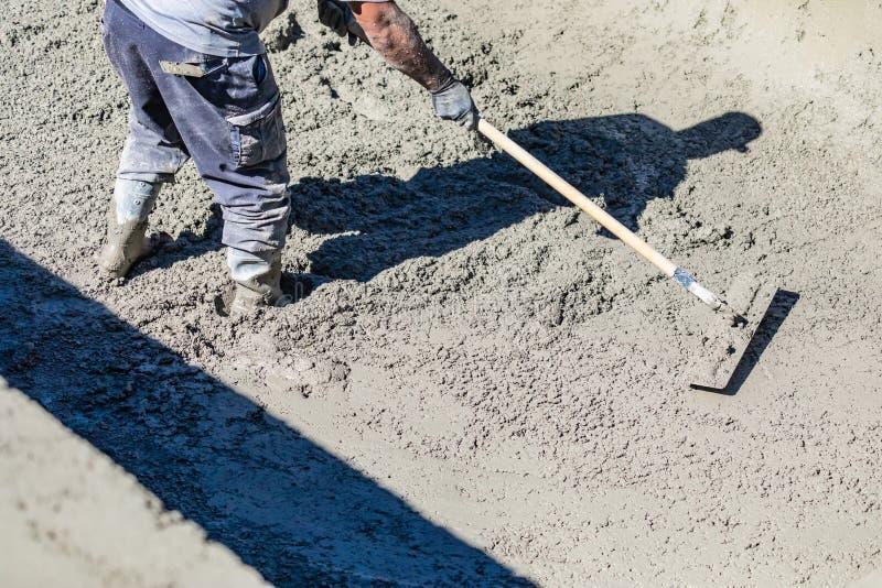 Funcionamento do trabalhador da constru??o da associa??o com um Bullfloat no concreto molhado fotografia de stock