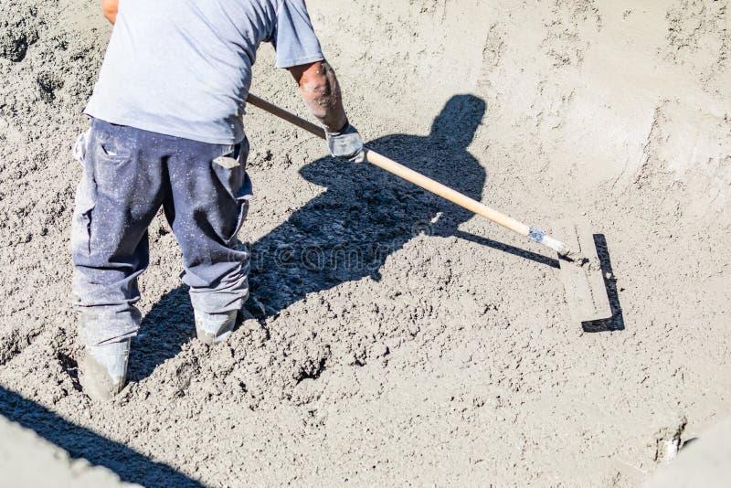 Funcionamento do trabalhador da constru??o da associa??o com um Bullfloat no concreto molhado fotos de stock royalty free