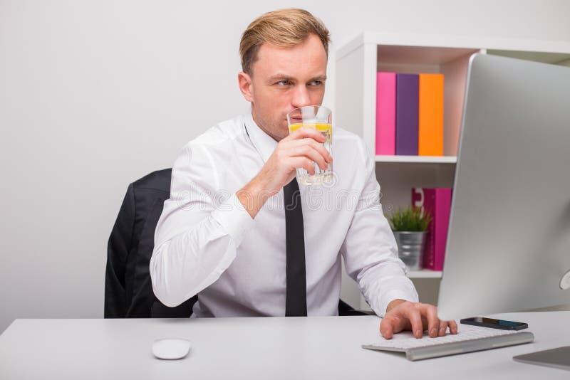 Funcionamento e água potável do homem no escritório fotografia de stock