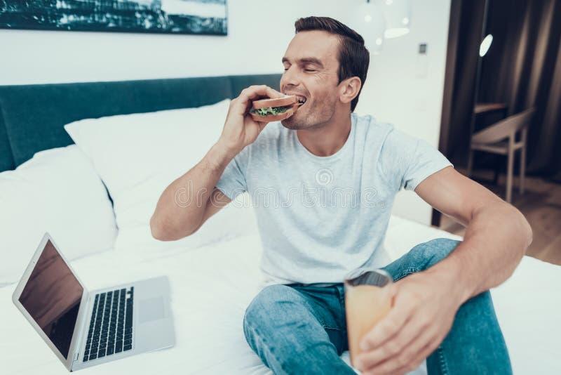 Funcionamento e apreciação de sorriso do homem do café da manhã na cama fotografia de stock