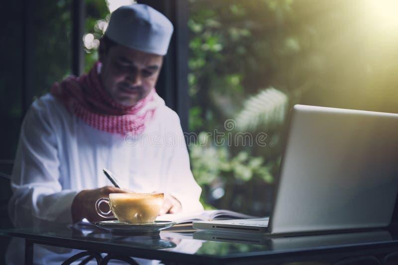 Funcionamento e escrita muçulmanos árabes do homem de negócios com o caderno no caf imagens de stock royalty free
