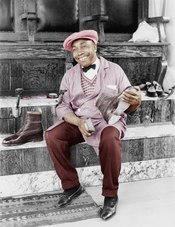 Funcionamento e sorriso do homem do engraxamento de sapatos (todas as pessoas descritas não são umas vivas mais longo e nenhuma p imagens de stock royalty free