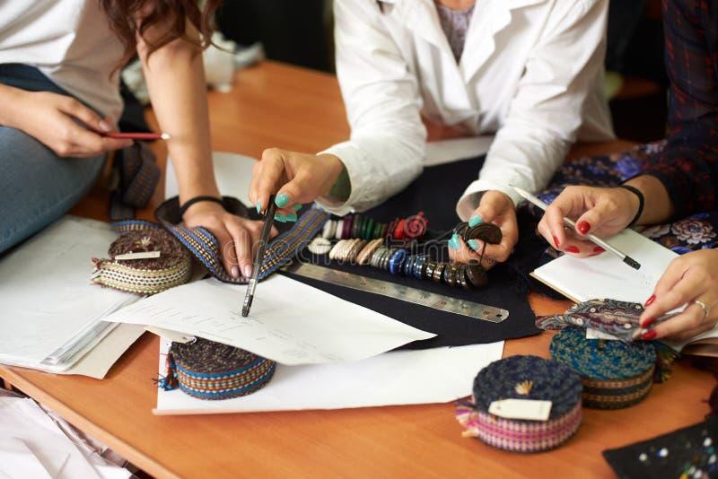 Funcionamento fêmea da equipe do desenhador de moda na criação da roupa, escolhendo os acessórios, discutindo esboços fotografia de stock