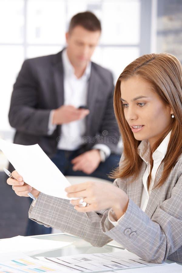 Funcionamento fêmea novo com papéis no escritório foto de stock royalty free