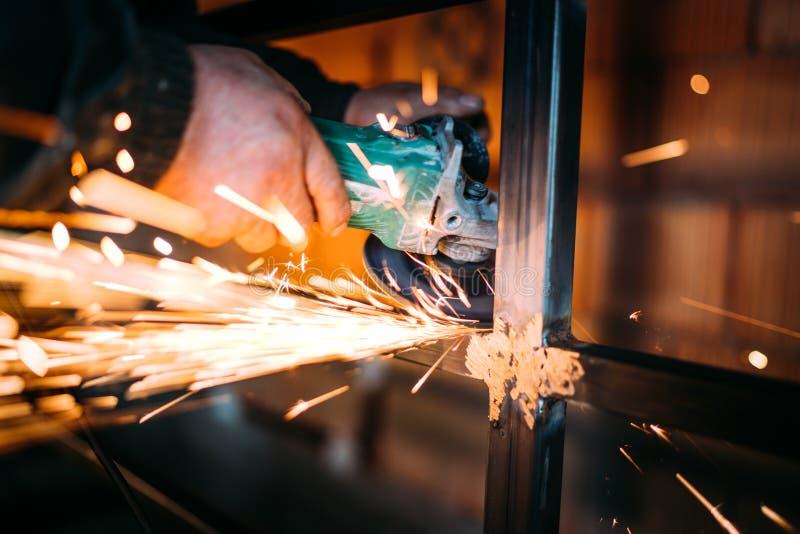 Funcionamento masculino caucasiano na indústria da construção civil e no metal do corte com o moedor de ângulo do disco foto de stock royalty free