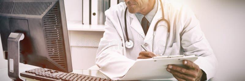 Funcionamento masculino concentrado do doutor imagem de stock royalty free