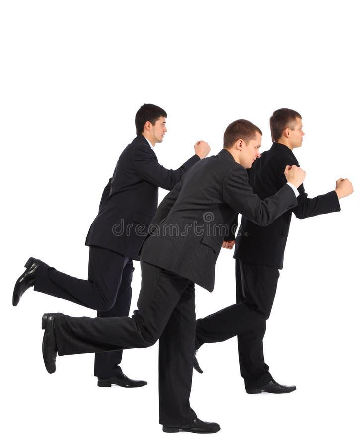 Funcionamento novo de três homens de negócios, vista lateral imagem de stock