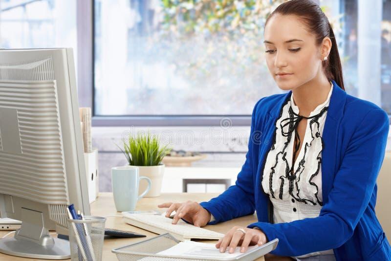 Funcionamento ocupado bonito da menina de escritório foto de stock royalty free