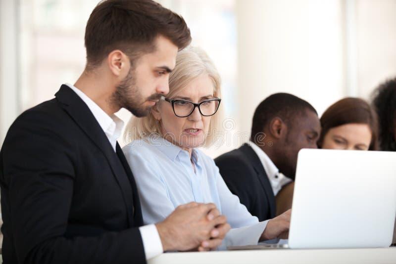 Funcionamento ocupado focalizado dos trabalhadores diversos no portátil na instrução imagens de stock royalty free