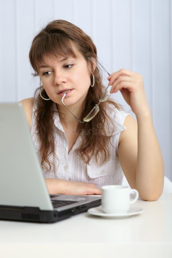 Funcionamento pensado da mulher nova com computador foto de stock