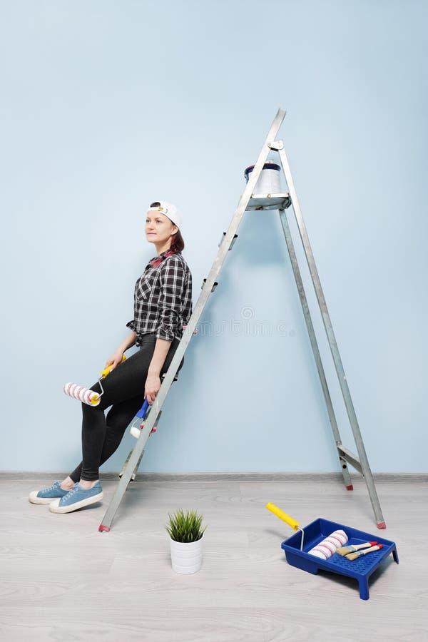 Funcionamento, pintor, assento no assoalho e vista da menina da parede Escolhe, pensa, restos, ao lado dele vai um animal de esti fotografia de stock