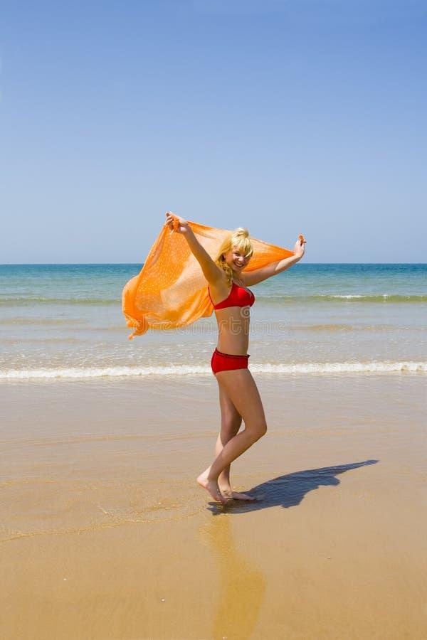 Funcionamentos da menina na praia imagem de stock